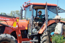 Photo of Daniel learning to drive the tractor